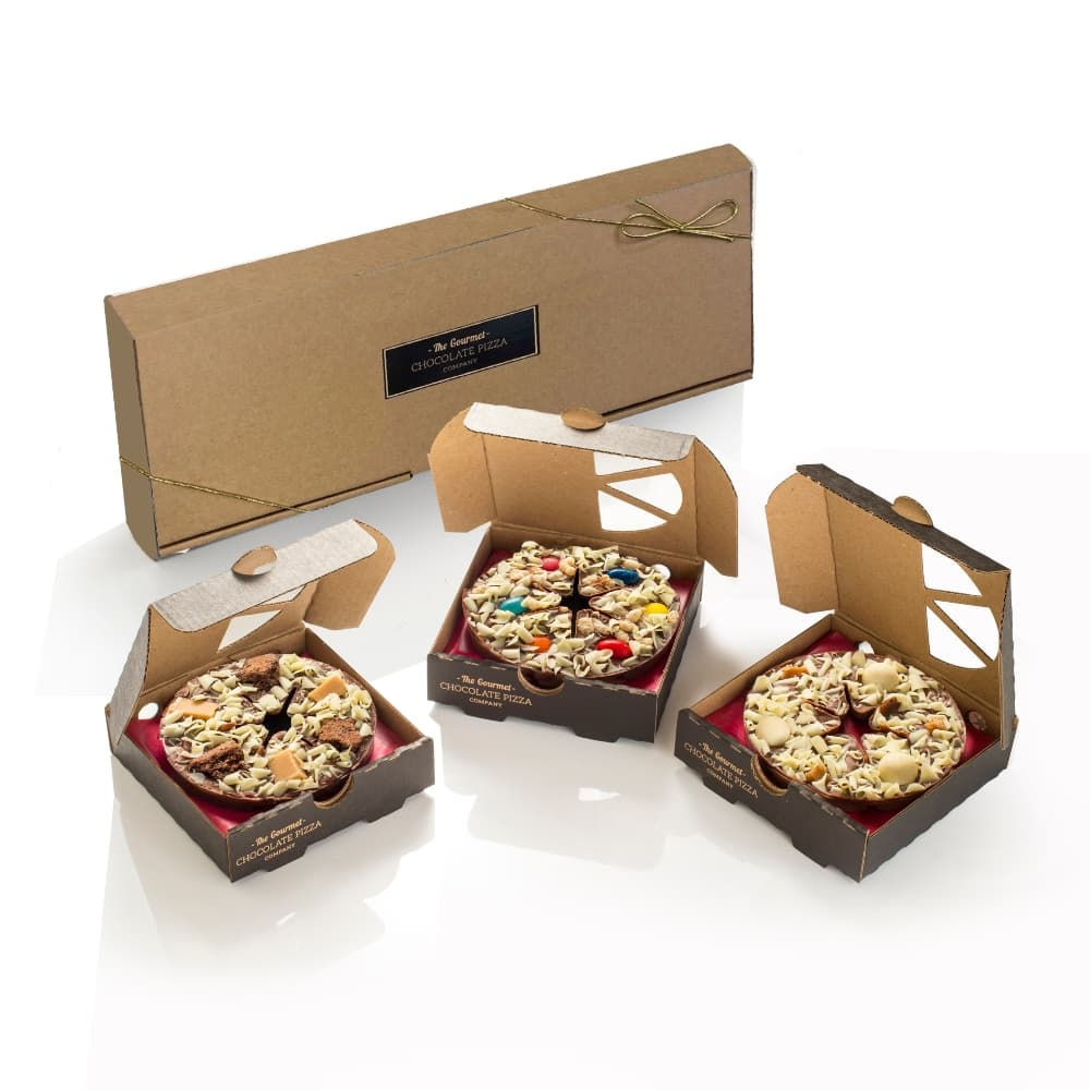 A trio of mini chocolate pizzas, presented in a kraft brown gift box